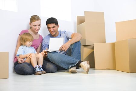 Young parents with daughter sitting on the floor between cardboard boxes. They're looking at laptop. Low angle view. Stock Photo - 3618316