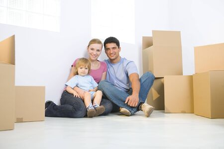 fatherhood: Young parents with daughter sitting on the floor between cardboard boxes. Theyre looking at camera. Low angle view.