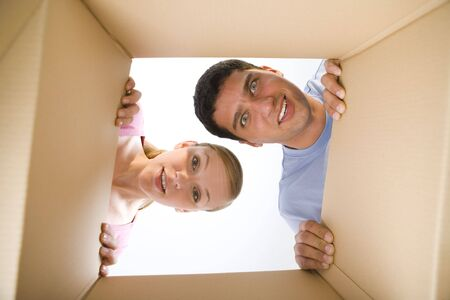 Young couple looking into cardboard box. They look like surprised. Looking at camera. Low angle view. Stock Photo