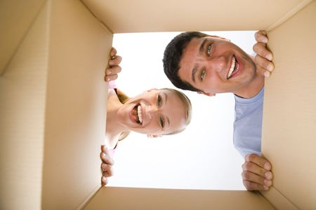 happy couple house: Young happy couple looking into cardboard box. Theyre looking at camera. Low angle view.