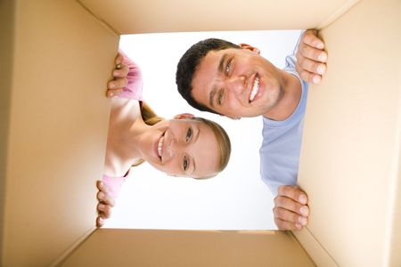 into: Young smiling couple looking into cardboard box. Theyre looking at camera. Low angle view.