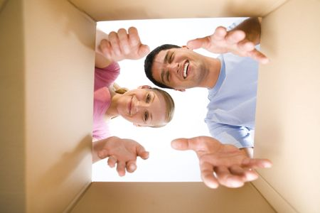homeowner: Young couple taking out something from cardboard box. Theyre looking at camera. Low angle view. Stock Photo