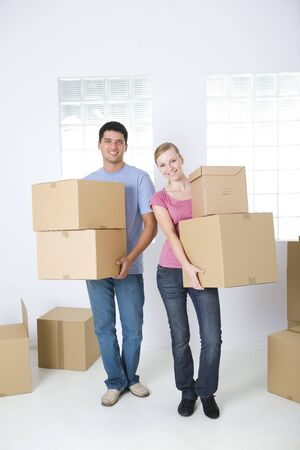 happy couple house: Young couple holding cardboard boxes. Theyre smiling and looking at camera. Front view.  Stock Photo