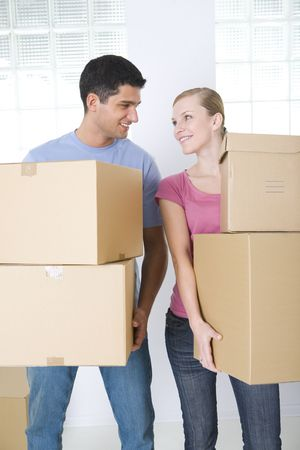 Young couple holding cardboard boxes. They're smiling and looking at each other's. Front view.  Stock Photo - 3618327