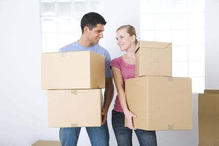Young couple holding cardboard boxes. They're smiling and looking at each other's. Front view. Stock Photo - 3618301