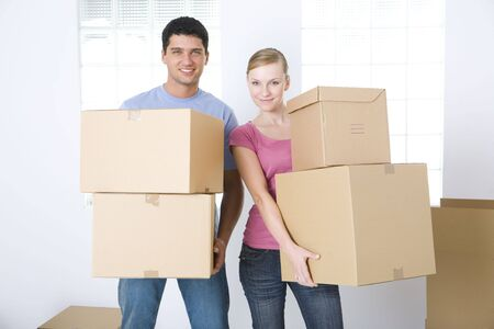 domestic life: Young couple holding cardboard boxes. Theyre smiling and looking at camera. Front view.  Stock Photo