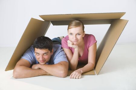 homeowner: Young smiling couple lying in cardboard box. Theyre looking at camera. Front view.