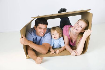 Young parents with their daughter lying in cardboard box. Theyre smiling and looking at camera. Front view.