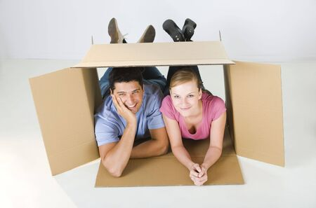 caucasian: Young smiling couple lying in cardboard box. Theyre looking at camera. High angle view.
