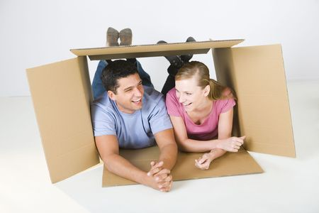 Young smiling couple lying in cardboard box and talking. Front view. Stock Photo - 3618318