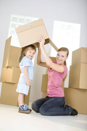 A woman with young girl are between cardboard boxes. A woman taking off cardboard box from head young girl. Theyre looking at camera. photo