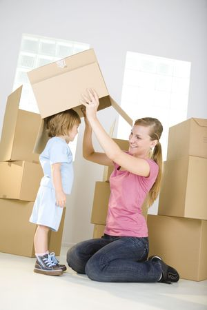 A woman with young girl are between cardboard boxes. A woman taking off cardboard box from head young girl. photo