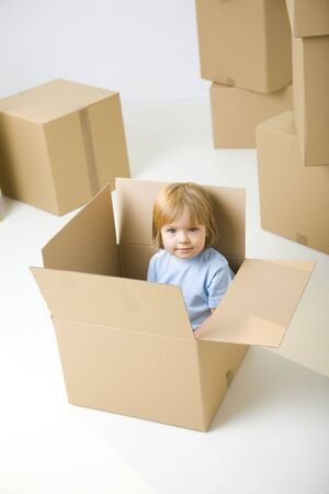 Young girl sitting in cardboard box between other boxes. Shes smiling and looking at camera.