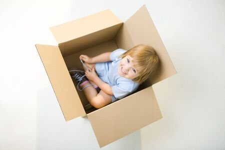 Young smiling girl sitting in cardboard box. Shes looking at camera. High angle view. Stock Photo
