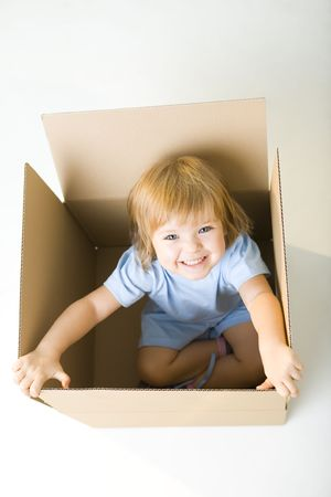 Young happy girl sitting in cardboard box. Shes looking at camera. High angle view. Stock Photo