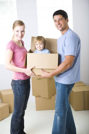 fatherhood: Young parents standing between cardboard boxes. Theyre holding one box with their daughter. Theyre looking at camera. Front view.