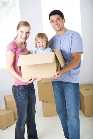Young parents standing between cardboard boxes. Theyre holding one box with their daughter. Theyre looking at camera. Front view.