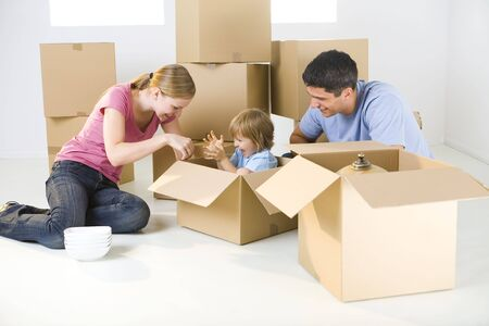 Young parents and their daughter sitting beside cardboard boxes. Young girl sitting in box.