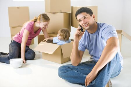 focused: Young parents and their daughter sitting beside cardboard boxes. Young girl sitting in box. Theyre smiling. A man talking by cellphone. Focused on man.