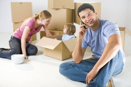 Young parents and their daughter sitting beside cardboard boxes. Young girl sitting in box. Theyre smiling. A man talking by cellphone and looking at camera. Focused on man. photo