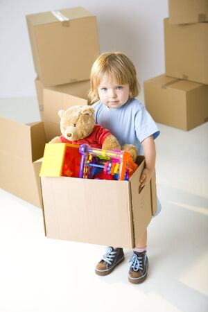 carry on: Young girl standing between cardboard boxes and holding box with her toys. Shes looking at camera. Stock Photo