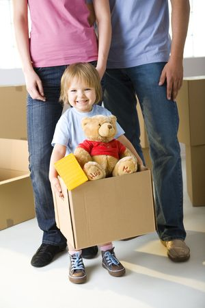 beside: Young girl standing beside her parents. Shes holding box with her toys. Shes smiling and looking at camera.