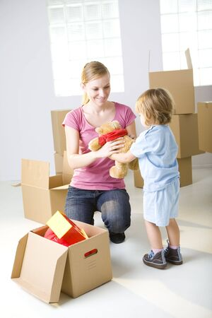squat: Young mother with her daughter are between cardboard boxes. A woman taking teddy bear from daughter.