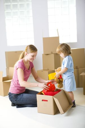 Young mother with her daughter sitting between cardboard boxes. A woman taking toy from box. Young girl holding teddy bear.  Stock Photo