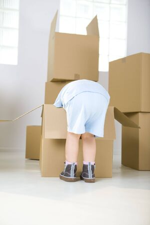 beside: Young girl standing beside cardboard boxes. Shes bending to one box.