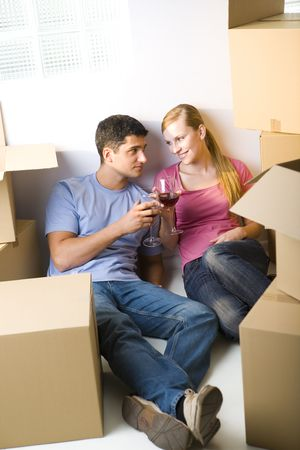 Young couple sitting between cardboard boxes and drinking wine. They're looking at each other's. Front view. Stock Photo - 3618333