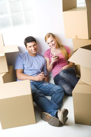 Young couple sitting between cardboard boxes and drinking wine. They're smiling and looking at camera. Front view. Stock Photo - 3618330