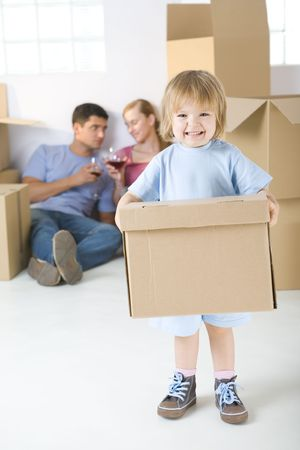 alcohol cardboard: Young parents sitting beside cardboard boxes and drinking wine. Theirs daughter standing in frond and holding box. Shes looking at camera. Stock Photo