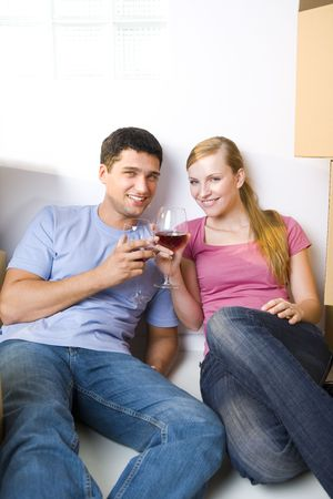 Young couple sitting between cardboard boxes and drinking wine. They're smiling and looking at camera. Front view. Stock Photo - 3618334