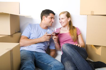 homeowner: Young couple sitting between cardboard boxes and drinking wine. Theyre looking at each others. Front view. Stock Photo