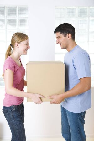 unpacking: Happy couple holding one cardboard box. Theyre looking at each others. Side view.