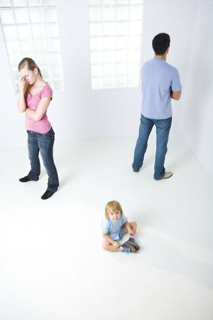 veszekedés: Young parents standing back to back. Theirs daughter sitting on the floor and looking at camera. High angle view.