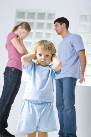 The young marriage quarreling. Theirs daughter stops her ears. Focused on young girl. Low angle view. Stock Photo
