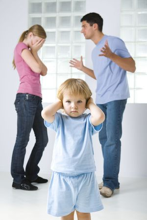 controversy: The young marriage quarreling. Theirs daughter stops her ears. Focused on young girl.