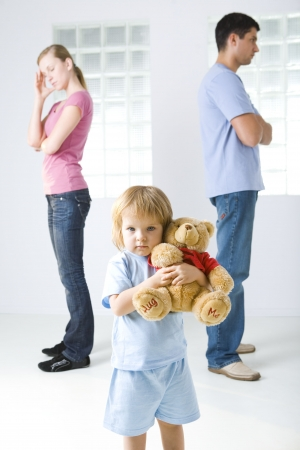 Young parents standing back to back. Theirs daughter huging teddy bear and looking at camera. Stock Photo