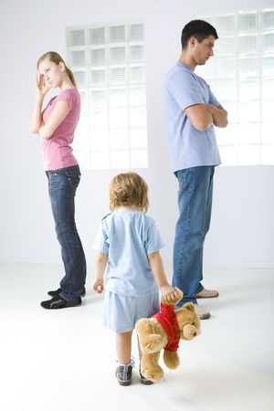 Young parents standing back to back. Theirs daughter holding teddy bear. Shes standing back to camera.