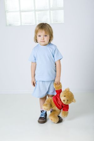 Young sad girl standing and holding teddy bear in heand. She's looking at camera. Front view. photo