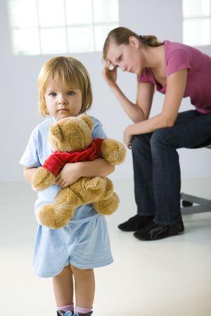 bambini tristi: Giovane ragazza in piedi con orsacchiotto e guardando fotocamera. Sua madre seduta dietro e di pensare. Incentrato sulla ragazza.