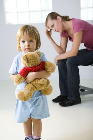 sad child: Young girl standing with teddy bear and looking at camera. Her mother sitting behind and thinking. Focused on young girl.