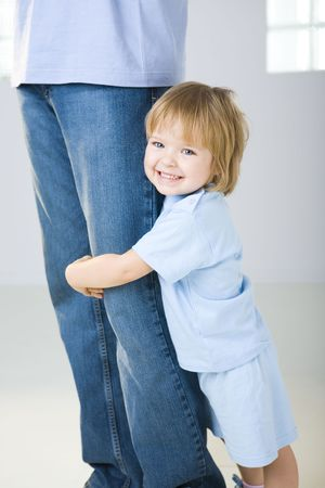 Young girl huging mans legg. Shes looking at camera. Focused on young girl.