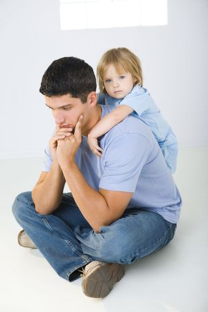 annoyance: A man sitting on the floor with cross-legged and his daughter huging him. A man looks like thoughtful. Stock Photo