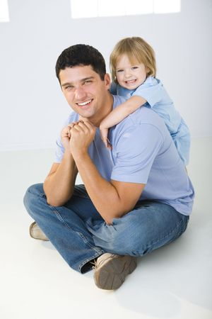 A man sitting on the floor with cross-legged and his daughter huging him. Theyre smiling and looking at camera.