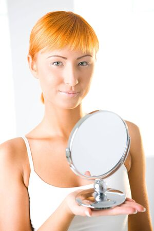 Young woman holding mirror. Shes looking at camera. Front view. photo