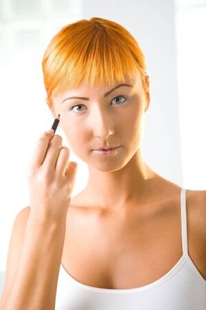 Young red-haired woman using eyeliner. Shes looking at camera. Front view. photo