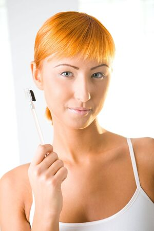 Young sexy woman with makeup brush. Shes looking at camera. Front view. photo