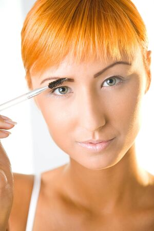 Young woman making her makeup. Shes looking at camera. Closeup on face. Front view. photo